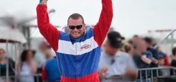 Stock car driver with hands up