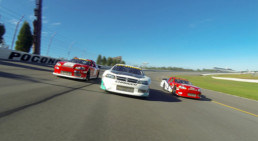 Three stock cars racing at Pocono Raceway