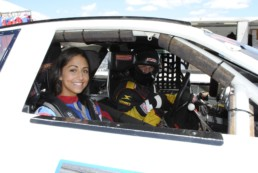 Passenger and driver in stock car