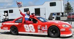 Girl waving flag in NASCAR style stock car